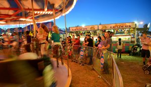 Classic County Fair scene from Thursday evening include  a mom and kids riding the carousel while others watch.