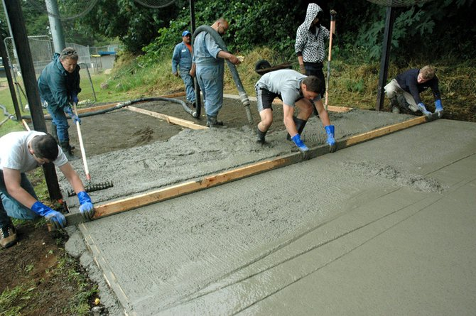 collins field will have a new addition next baseball season: new concrete for its batting cages. Above, Kristian Apland gets help on the project; below is Apland at work.