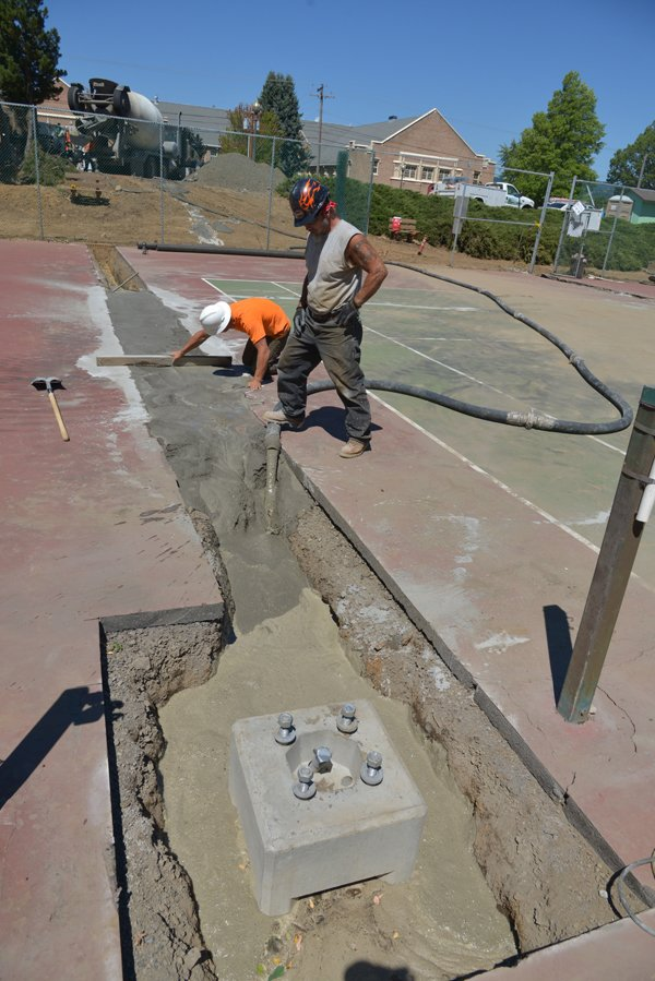 concrete was poured Thursday to fill trenches dug to bury electrical conduit for new light poles.