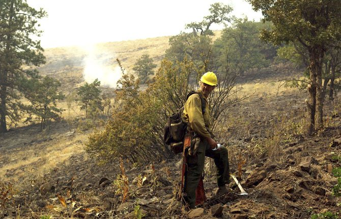 FIREMAN WORKS, above, on a fire break at Mile Marker 28 near Goldendale. Highway 97 remains closed until further notice and residents have been placed on notice to evacuate if the danger level becomes too high.