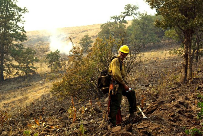 A firefighter pauses while working on the Mile Marker 28 fire near Goldendale. Firefighters spent Tuesday building new control lines.