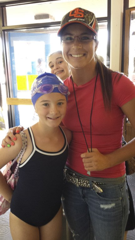 Eight-year-old Lucy Booth, left, of The Dalles Swim Team, is pictured with assistant coach Katelyn Bailey at the state 12 and under longcourse swim meet in Albany in July.
