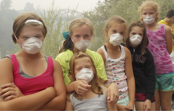Smoky Haze Covers State  Members of the Firesliders softball team from Portland, Ore., wear masks to keep out smoke from wildfires as they wait to board a jetboat in Grants Pass to take a ride on the Rogue River on July 31. In the forests of southwest Oregon, firefighters and support crews now number more than 4,000 people with more on the way. Five crews of 10 people each are expected to arrive Friday, five more on Sunday.