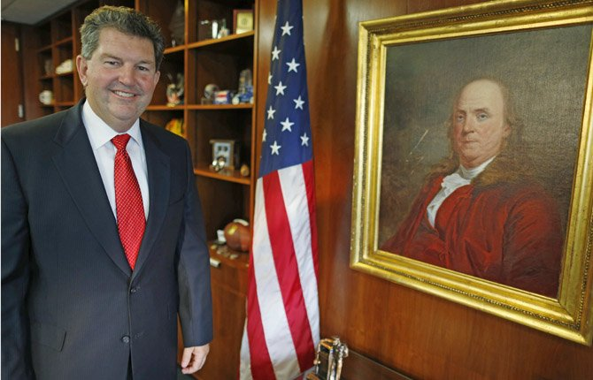 POSTMASTER GENERAL Patrick R. Donahoe poses with next to a portrait of Benjamin Franklin, the first postmaster general, after an interview with the Associated Press at his office at U.S. Postal Service Headquarters in Washington on Aug. 1. Donahoe has a wish list for raising cash for his financially ailing agency. High on it is delivery of beer, wine and spirits. In an interview with The Associated Press, Donahoe also endorsed ending most door-to-door and Saturday mail deliveries as cost-saving measures.