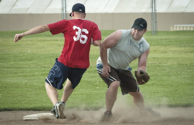 Travis Church of Gary Denney Floor Covering (McGlovin), left, avoids a tag by Pete Hall of Amerities but is called out for overrunning second base.