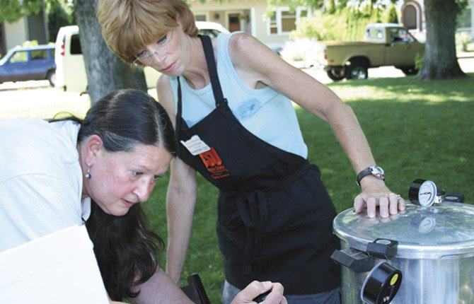 Marcia Strader, left, and Karen Peruzzo (both Master Food Preservers) test a Pressure Canner at the Farmer's Market.