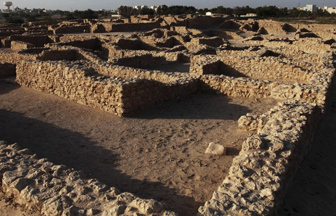A Bronze-age settlement is seen near the encroaching modern village of Saar, Bahrain. The settlement. with still more than 70 ruins, was built more than 4,000 years ago and remained in use for 150 to 200 years, according to archaeologists. The settlement built in northern Bahrain includes a temple, dwellings and a honeycomb-like graveyard.