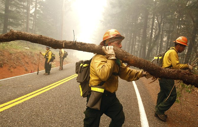The Dalles, Ore. firefighters Mario Carmona, middle, and Ismael Vega, right, help clear brush and trees near a home in Wolf Creek, Ore. July 31, 2013.