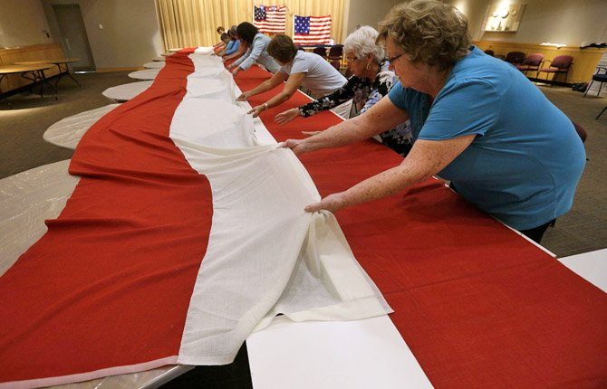 In this July 22, 2013 picture, volunteers line up stripes that, when hand-stitched together, will be part of a replica of the star-spangled banner in Baltimore. It was 200 years ago this summer that a Baltimore flag-maker stitched the flag that inspired America's national anthem. Now, hundreds of people are helping to recreate the star-spangled banner. The project began July 4 in Baltimore, and it is expected to take volunteers six weeks to hand sew the estimated 150,000 stitches in the famous flag. When finished, it will be about a quarter of the size of a basketball court.