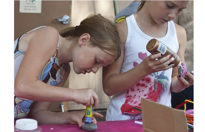 ZOE DUNN, 8, LEFT, AND ASHLEY QUISENBERRY, 9, decorate a pair of pet rocks during a Summer Reading focus on rocks and minerals at The Dalles Wasco County Library Aug. 1.