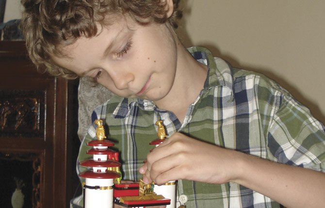 "Theron Bowman, 7, describes a chapter in his book, Neverwinter Nights 4, as depicted in a Lego model he created. He loves to refashion Lego pieces into his own creations, which he calls ""Make it up again."""