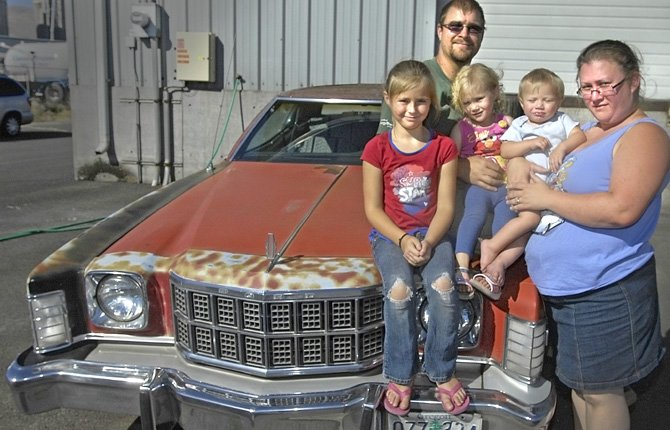THE VOLLMAR family braves Tuesday's heat and winds to take a photo with the 1974 Ford Grand Torino that will one day belong to Andrew, 1, who is held by mom, Melissa, at right. Jean, 7, left, and Nina, 3, are waiting for select models from their favorite TV shows to get in on the deal that trades good grades and behavior for a set of car keys when they turn 18. Ben, back, has been interested in classic cars since the age of 6  and is sharing that passion with his children as a way to teach them that there are rewards for hard work and perseverance.