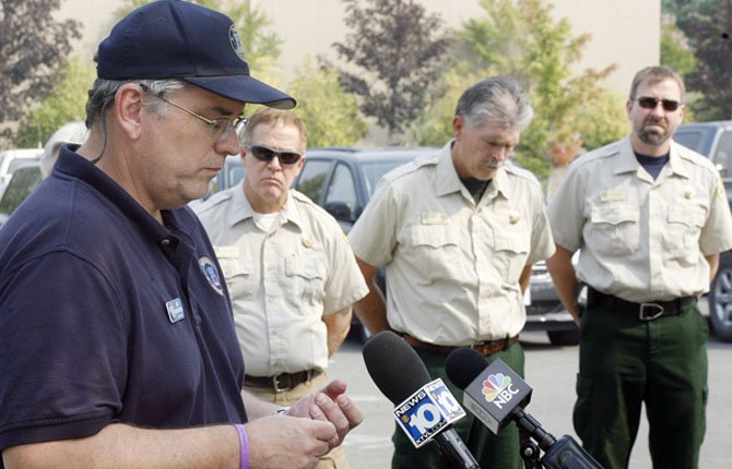 Jim Whittington BLM fire information officer, left, pauses momentarily to regain his composure during a news conference addressing the death of Jesse Trader, 19, a water tender truck driver who died in a roll-over on Bear Camp Road Tuesday, Aug. 6.