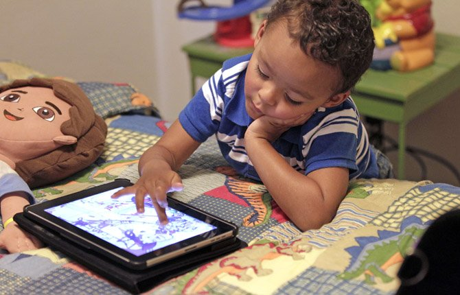 Frankie Thevenot, 3, plays with an iPad in his bedroom at his home in Metairie, La. As of Wednesday, Aug. 7, the Campaign for a Commercial-Free Childhood, a Boston-based group, is urging federal investigators to examine marketing practices of Fisher-Price's and Open Solution's mobile apps.