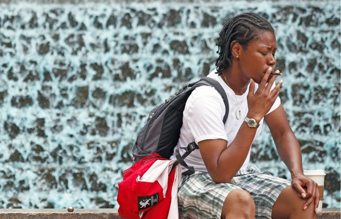 "Venisha Smalls, 35, of Atlanta, takes a smoke break July 26 next to a fountain in Woodruff Park in Atlanta. ""No Smoking"" signs are going up in parks, beaches and other outdoor venues across the country, but some experts are questioning whether there's enough medical evidence to support the trend."