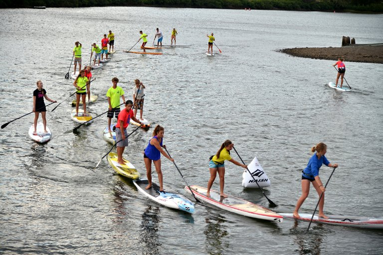 MORNING WORKOUTS for 30 members of this summer's Big Winds SUP team include stretching, yoga and strength training (right) and on-the-water drills like sprints and buoy practice.