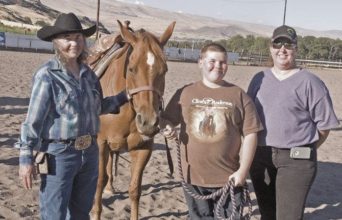 FOR GENNY OLMSTEAD, left, 4-H is about more than just horses and blue ribbons. It's also about friends and family including Brandon Ringlbauer, 12, center, and her daughter Denise Olmstead. The Moonlight Riders club that Genny Olmstead leads is also about giving club members skills to last a lifetime.