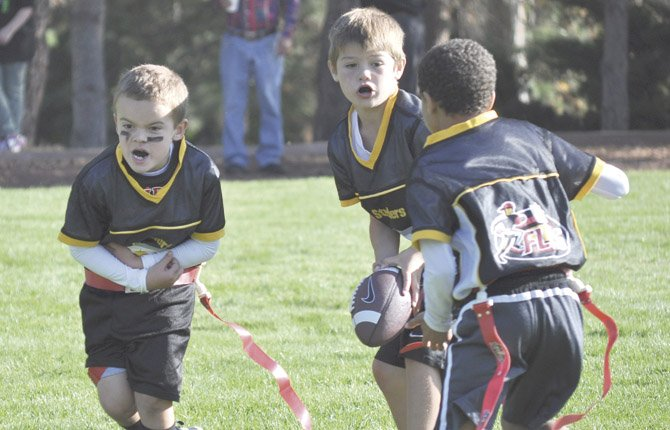 THE DALLES Youth Flag Football player Quincy Townsend (left) feinds handoff while quarterback Kade Wilson (with ball) gets set to make a pitch to Styles DeLeon in a game last season at Wahtonka Fields. TDYF has extended signups for flag football to Aug. 21 at midnight for any first-and-second grade boys and girls.
