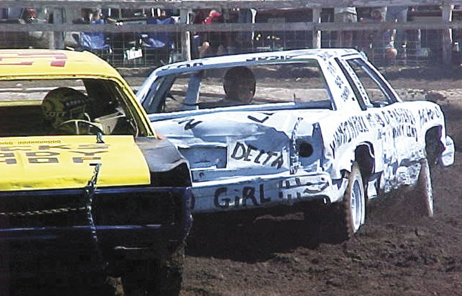 "JUDY EWING in the blue car, E80, where the ""E"" is in memory of her late mother, drove demolition derby cars for about five years at the Wasco County Fair. Her participation started as a result of a bar bet."