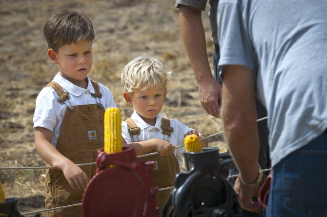 ZEBULEN STELZER, 5, left, and brother Zadion, 2, watch a demonstration of how corn kernels are removed from the cob with a hand-cranked machine at the Dufur Threshing Bee Saturday, Aug. 10.