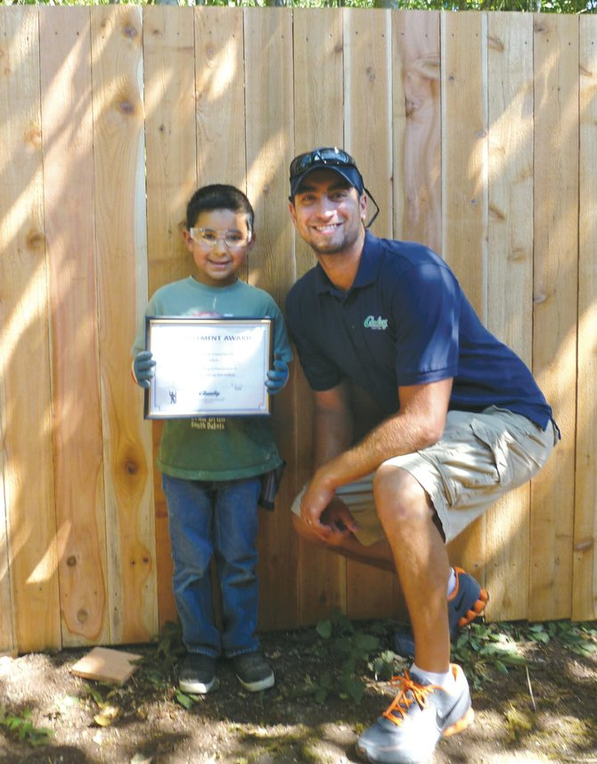 Former Sunnysider Joseph Chumley, now a contractor in the Puyallup area, believes in giving of himself to help others. Standing with him is one of Chumley's biggest fans. The five-year-old neighbor boy gained confidence in himself and how to work hard every day with Chumley's help. Here, Chumley gives the boy a certificate in honor of his accomplishments.