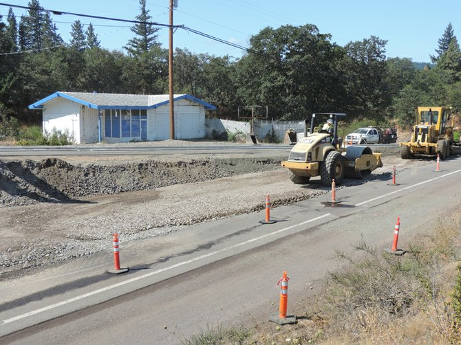 CRESTLINE CREWS prepare the final portion of the new road, and its intersection with Country Club, about 300 yards west of the current West Cascade-Country Club junction. (In background is the vacant gas station, formerly River's Edge Towing.)