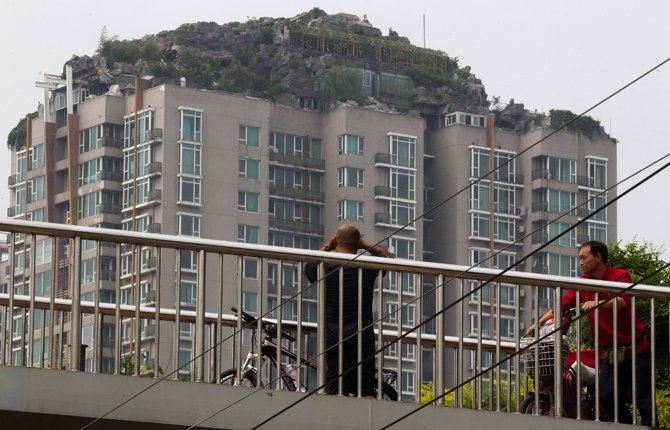A man looks at a roof top villa with binoculars from an overhead bridge in Beijing, China, Tuesday, Aug. 13, 2013. Beijing authorities are planning to demolish the bizarre rooftop villa embedded in rocks, trees and bushes that allegedly was built illegally atop a 26-story apartment block in the capital. 