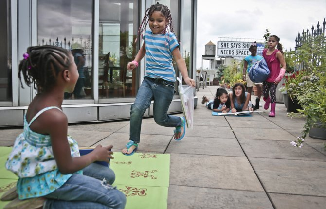 Youngsters attending LitCamp, a summer reading program offered through the nonprofit literacy organization LitWorld, find sections of a rooftop patio for their independent reading, in New York's Harlem neighborhood Aug. 7. 	AP Photo/Bebeto Matthews