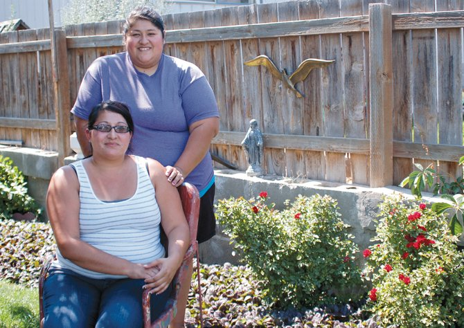 Sisters Amanda Rodriguez (seated) and Michelle Gonzalez daily help out with the chore of keeping their mother's garden healthy and inviting.