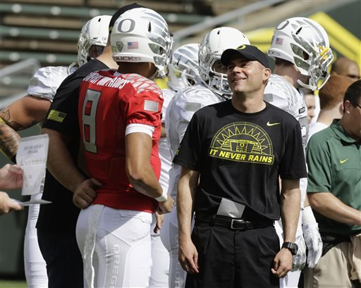 In this April 27, 2013, file photo, Oregon football coach Mark Helfrich, right, chats with quarterback Marcus Mariota during their spring NCAA college football game in Eugene.