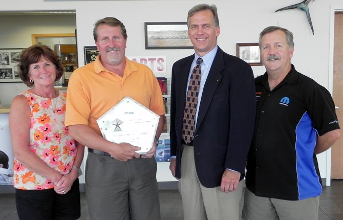 C.H. URNESS MOTOR CO. receives the Chrysler Corporation award for 50 years as a Chrysler dealer. Pictured, from left are Kathy Uhalde, C.H. Urness secretary-treasurer; Mike Urness, C.H. Urness president; Grant Biehler, Chrysler area sales manager; and Tim Urness, C.H. Urness vice president.	Chelsea Marr photo