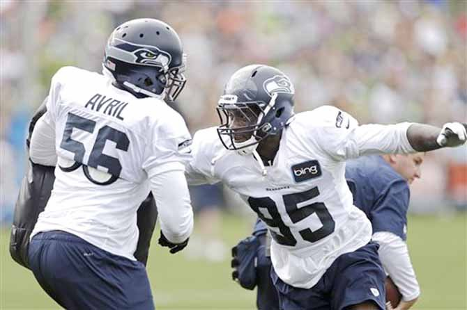 Seattle Seahawks' Benson Mayowa, right, runs through a drill with Cliff Avril during NFL football training camp Wednesday, Aug. 14, 2013, in Renton, Wash. Avril, a free-agent signing, saw his first action on the field.