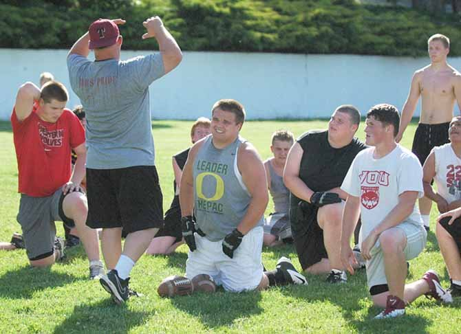 TDW football players (pictured from left), Connor Shortt, Mike Pifer, Justice Tyler and Riley Bardes listen to head coach Steve Sugg (front, left) during summer practice in The Dalles. The team will continue its season preparation for the rest of this week until kicking off schoolwide daily doubles on Monday, Aug. 19.