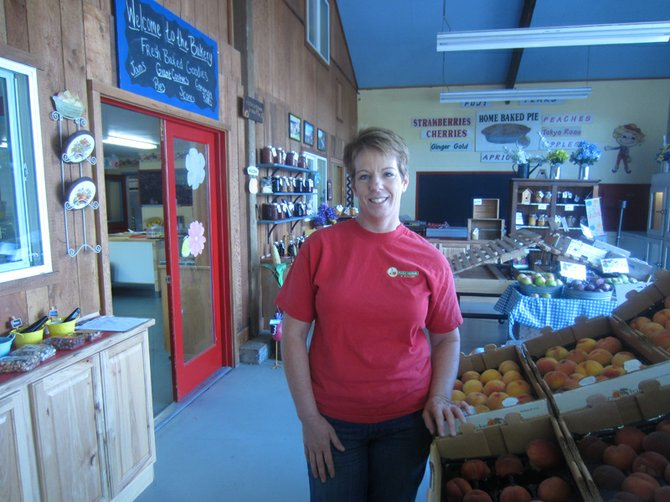 TAMMI PACKER takes a breather at her Odell business. The jams and other canned products are a local favorite, and the fruit stand boasts plenty of fresh seasonal fruit.