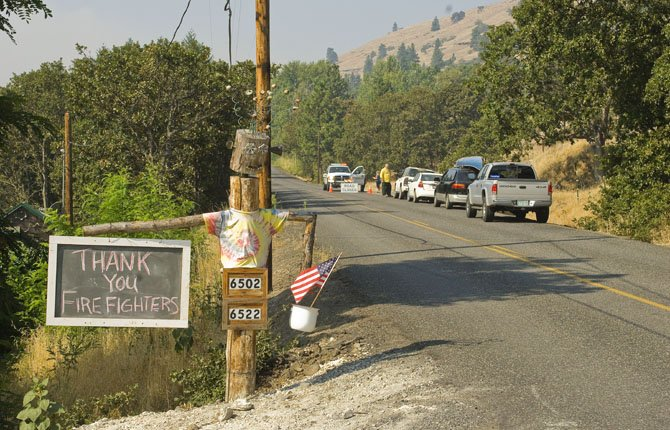 A message of gratitude hangs near where officials are turning cars back from a roadblock on Mill Creek Road.