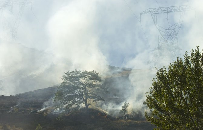 The fire burns above Reservior Road Tuesday afternoon.