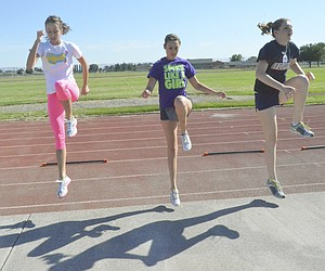 Jordyne Jaquish, a 2008 Sunnyside High School graduate just recently named the new head volleyball coach at SHS (at left), leads Ashley Davis (center) and Josie Marro (right) in conditioning drills yesterday afternoon. The 3:45 to 4:30 p.m. conditioning sessions are open to all prospective volleyball