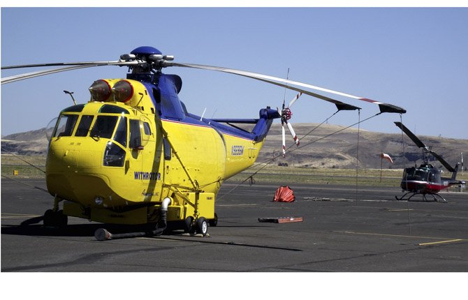 A YELLOW HELICOPTER, above, uses a siphon to load water and drops the load on the fire much like a retardant plane. At left, a Chinook helicopter lifts off headed toward a reservoir at a higher elevation in preparation to drop a load of water. People on the ground at the bottom of the photo, offer scale to show the size of the air ship.