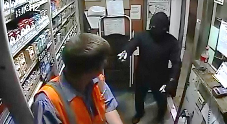 A gunman threatens the life of a 19-year-old Astro station clerk in a holdup the night of Aug. 13 in downtown Hood River. This image was taken from the station's security camera. The robber made off with approximately $200 in cash.