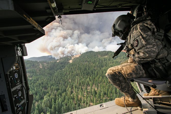 national guard crews arrived this week to help firefighting efforts on the Government Flats Complex. Pictured here, Sgt. Mike Buchan looks for spot fires from a  Blackhawk helicopter.