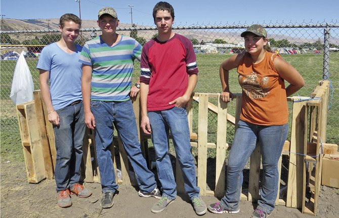 Teen helpers at the Government Flats Fire Complex base camp, from left to right, Ian Corey, J.R. Walker, Cole McDowell and Mary Jorgensen stand by a group of pallets they lashed together to provide a space for fire personnel to place cardboard boxes for recycling.