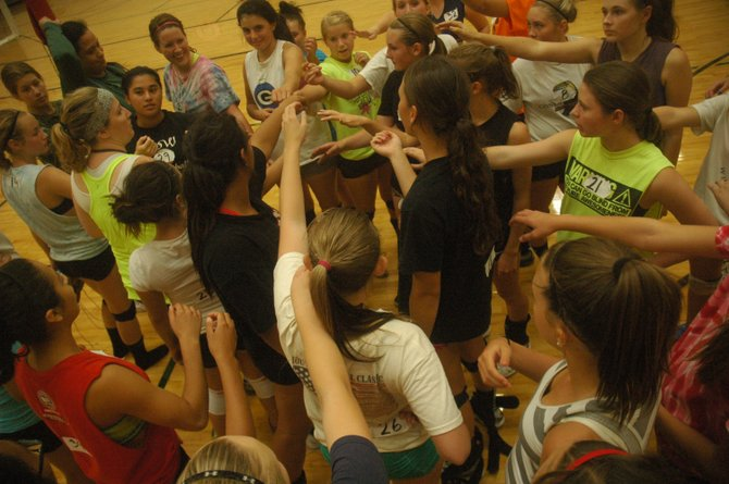 THE DALLES WAHTONKA coaches Kelly DeLeon (with headband in middle) and Neticia Enesi (all black in middle) lead an after workout cheer for the voleyball team after a second session of daily doubles. TDW has seen a swell in numbers this year, so competition has been fierce in camp as players vie for spots.