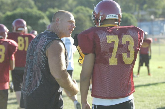 TDW coach Rich Belanger talks with linebacker Eric Morales in Monday's practice in The Dalles. Belanger is bringing the heat with a blitz-oriented defense to put some hits on opposing offense.