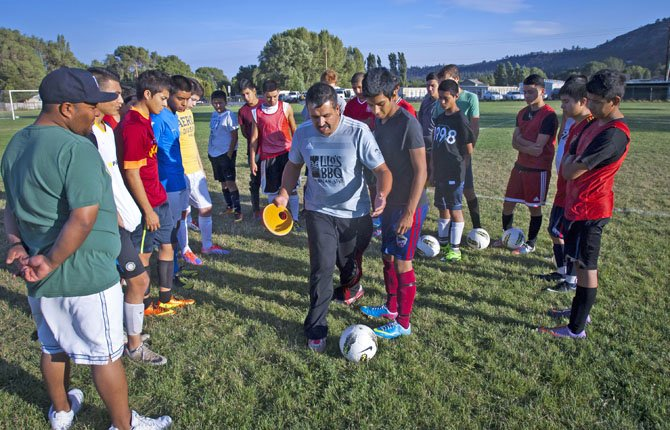 THE DALLES WAHTONKA boy's soccer coach Luis Gamez (middle) goes over a shooting drill with his players in Friday's practice at Wahtonka High School. With a group of eight seniors on the roster, the Eagle Indians have the experience and skills possible to make a run at a league crown and beyond.