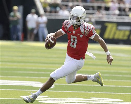 In this April 2013 photo, Oregon quarterback Marcus Mariota runs during the NCAA college football team's spring scrimmage in Eugene. Mariota is planning to take on more than just a few extra pounds this season. Oregon's soft-spoken quarterback, who bulked up with 12 pounds of muscle over the summer, says he's ready to break out and become a more vocal leader of the Ducks in his sophomore year.