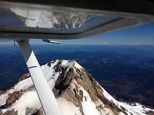 MOUNT HOOD in foreground,Mount Adams above right, Mount Rainier at the wing tip and Mount St. Helens hiding behind the pitot tube (which measures outside air pressure, temperature and density).
