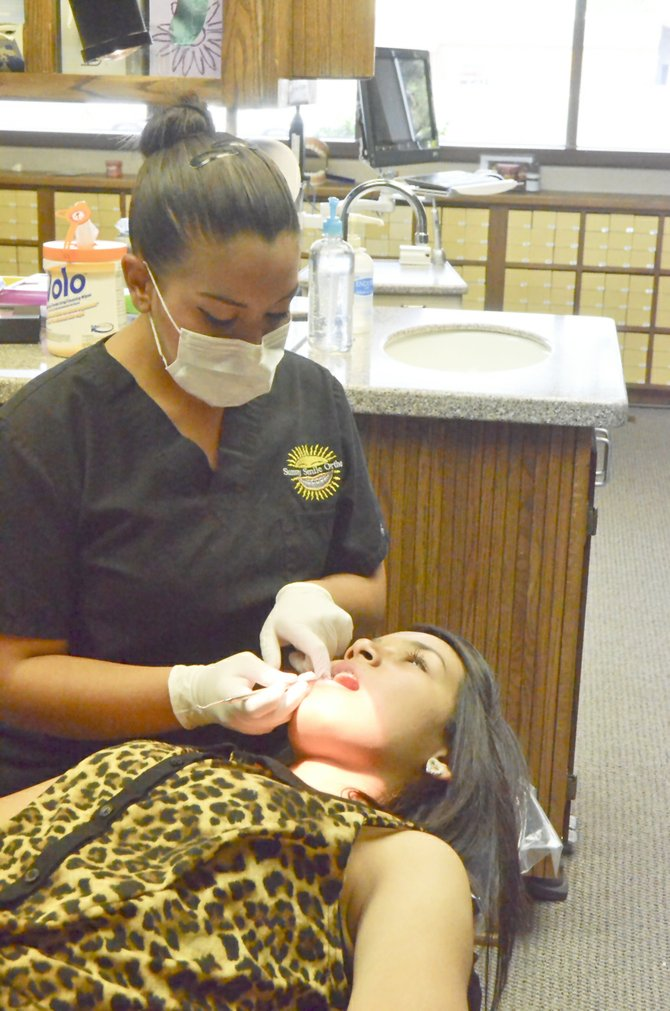 Sunny Smile Orthodontics Dental Assistant Jessica Guizar checks the braces on Cristina Espinoza during a recent visit.