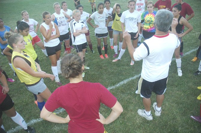 THE DALLES WAHTONKA girl's soccer players stand in unison while assistant coach Greg Burkart (bottom right) discusses team philosophy and season expectations at the end of Tuesday's practice. With a roster of 11 underclassmen and two seniors in Alicia Andersen and Bailey Cordell, the Eagle Indians will be young, but will be a group to keep an eye on this fall season.