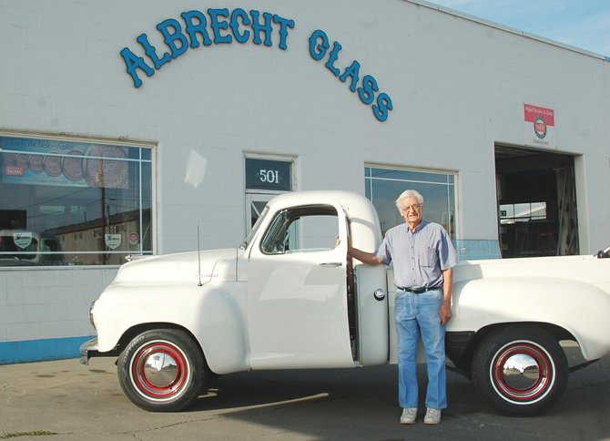 Chris Albrecht, founder of Albrecht Glass of Sunnyside, poses with his son Steve's fully restored 1952 Studebaker pick-up. Both the truck and the building behind it are historic Sunnyside landmarks.