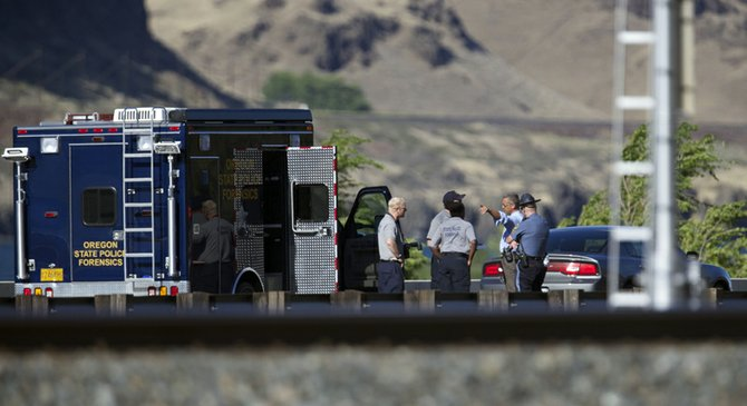 Oregon State Police investigators view a scene where a man died after exchanging gunfire with an Oregon State Police Trooper in the east-bound lanes of I-84 Thursday Aug. 29, 2013.  (AP Photo/The Oregonian, Randy L. Rasmussen)